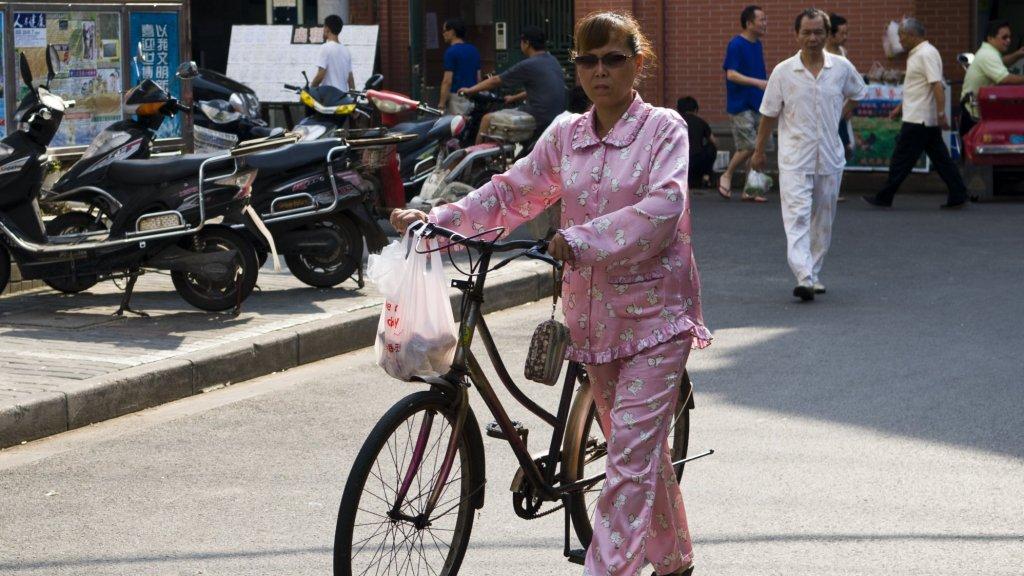 Een vrouw draagt een pyjama op straat in Shanghai.