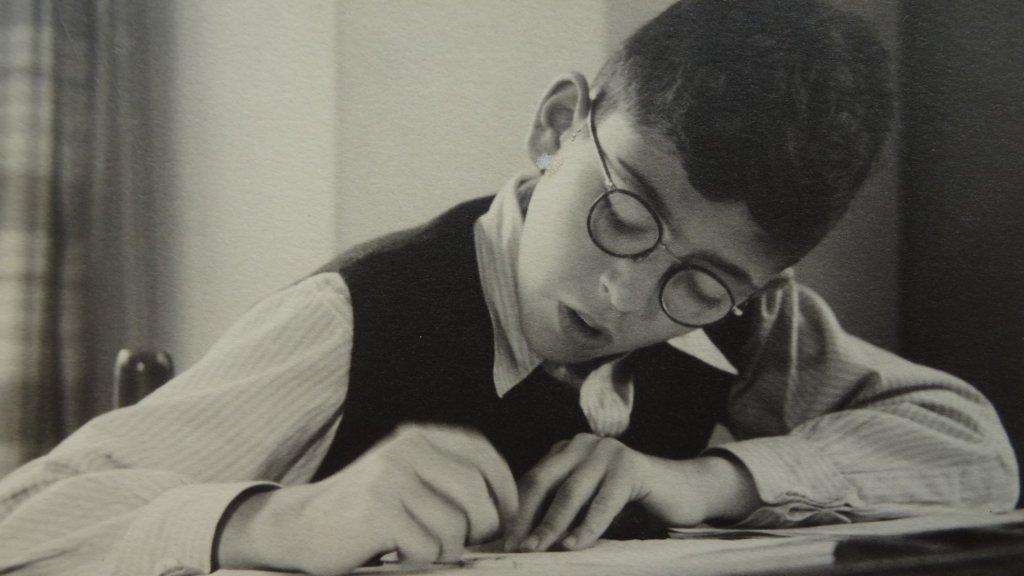 Erns Verduin als kind, tijdens het maken van zijn huiswerk