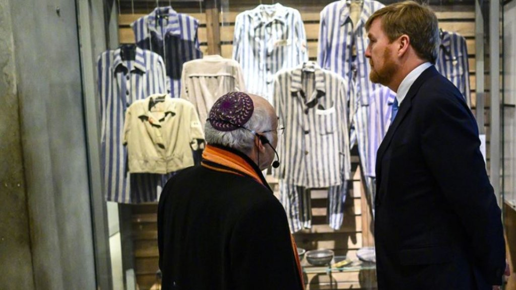 De koning voor een vitrine met gevangeniskleding van Holocaustslachtoffers