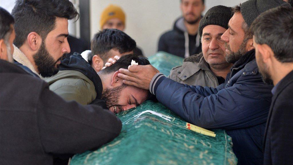 Een man rouwt om het verlies van een familielid.