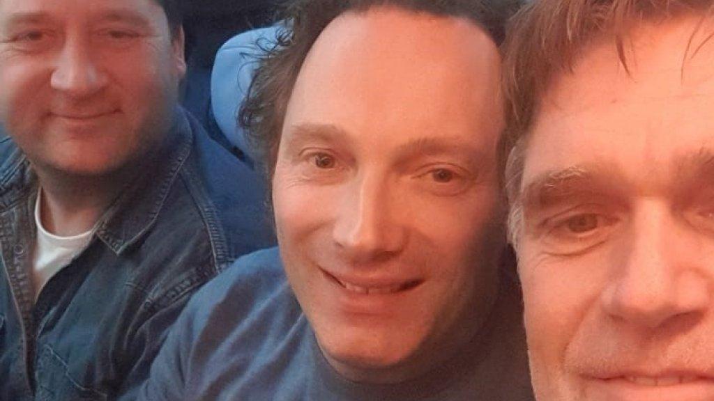 Mark (r) met zijn vrienden in het vliegtuig nadat de rust is teruggekeerd.
