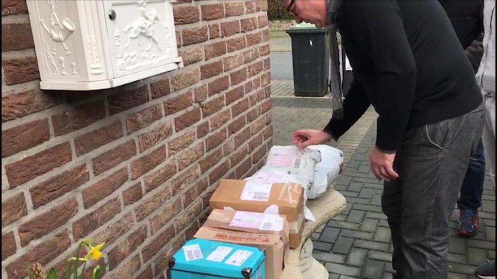 Bezorgers stapelen pakketjes bij het echtpaar tegen de gevel aan.