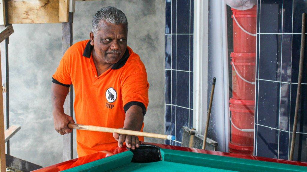 Een man speelt biljart in VHP-shirt.