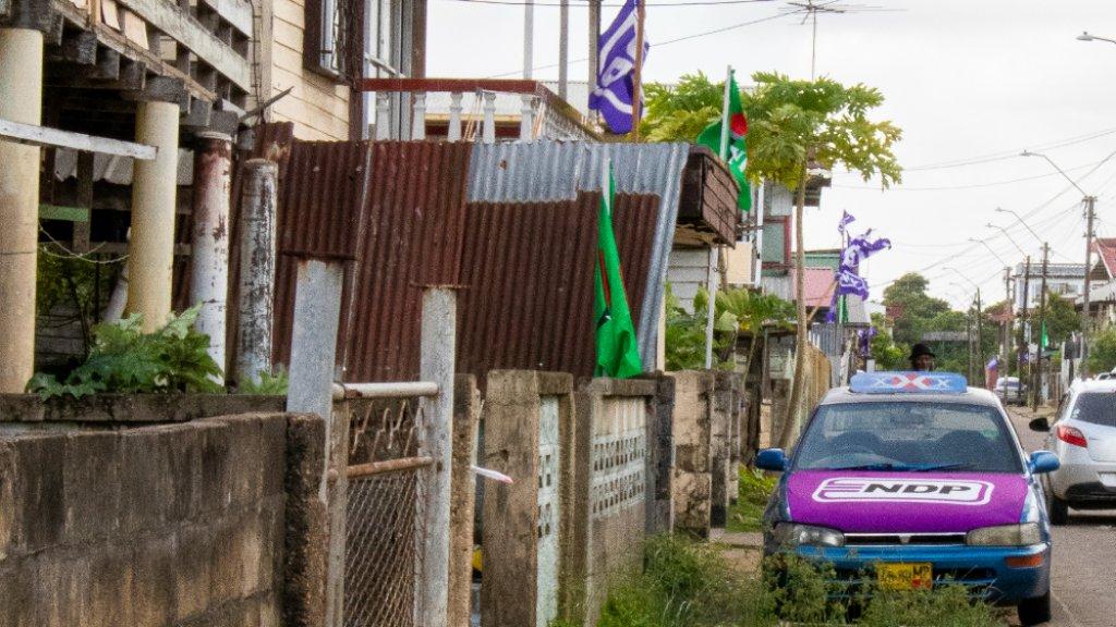 Een auto met daarop het NDP-logo, geparkeerd in een straat met NDP en NPS-vlaggen.