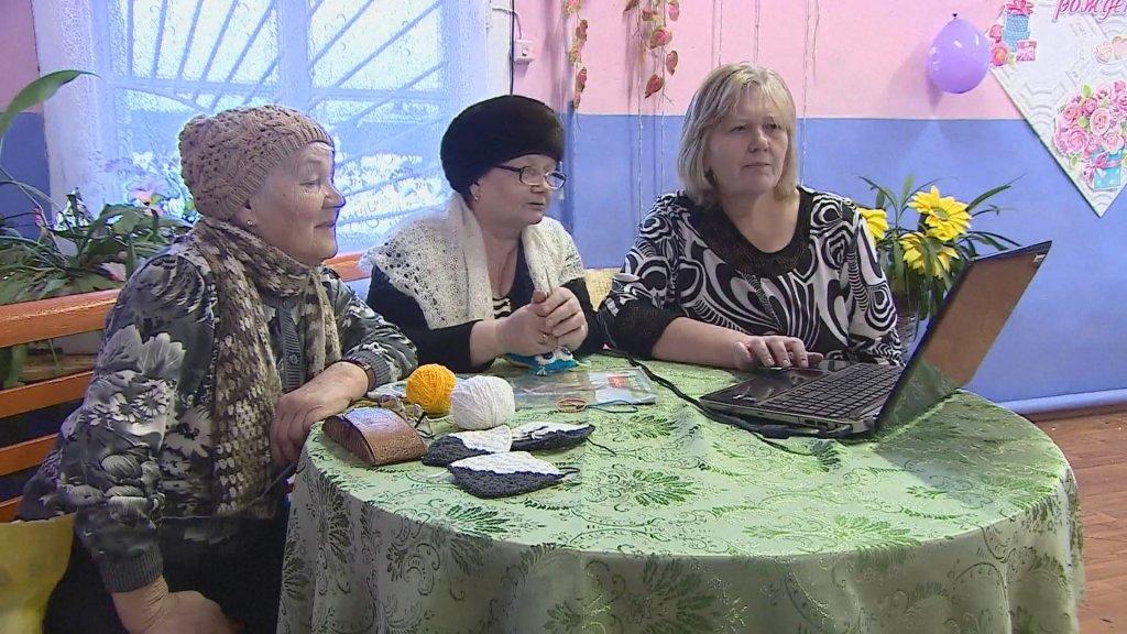 Vera Savina (rechts) met twee bibliotheekbezoekers en de bewuste laptop.