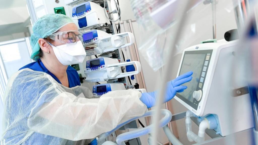 Een verpleegkundige draagt een mondkapje op een ic-afdeling