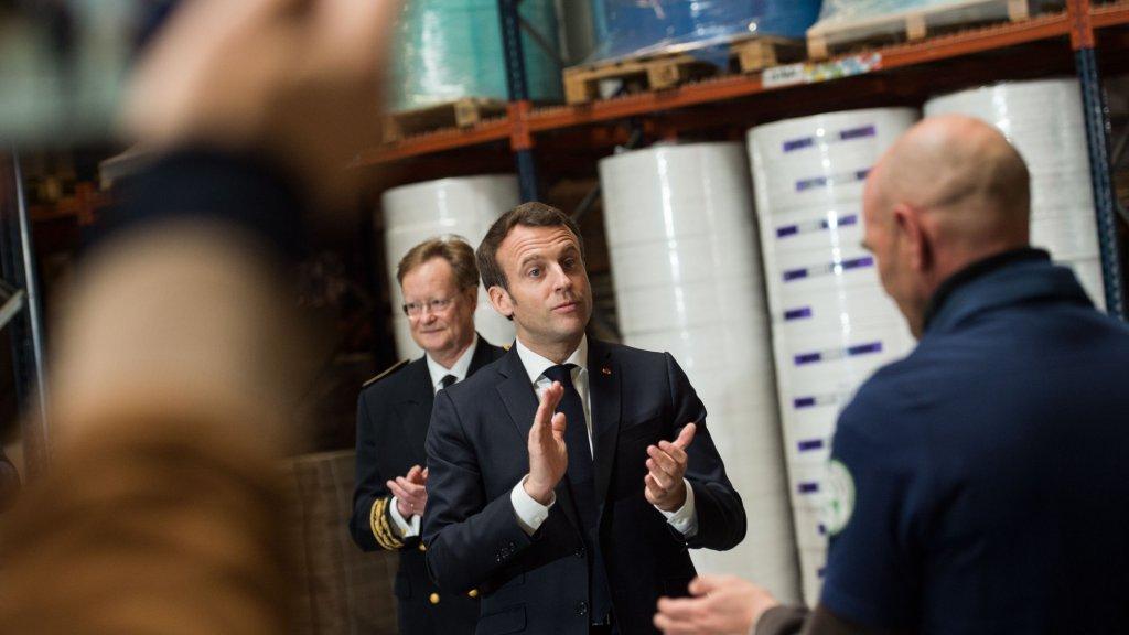 President Macron bezoekt een mondkapjesfabriek.