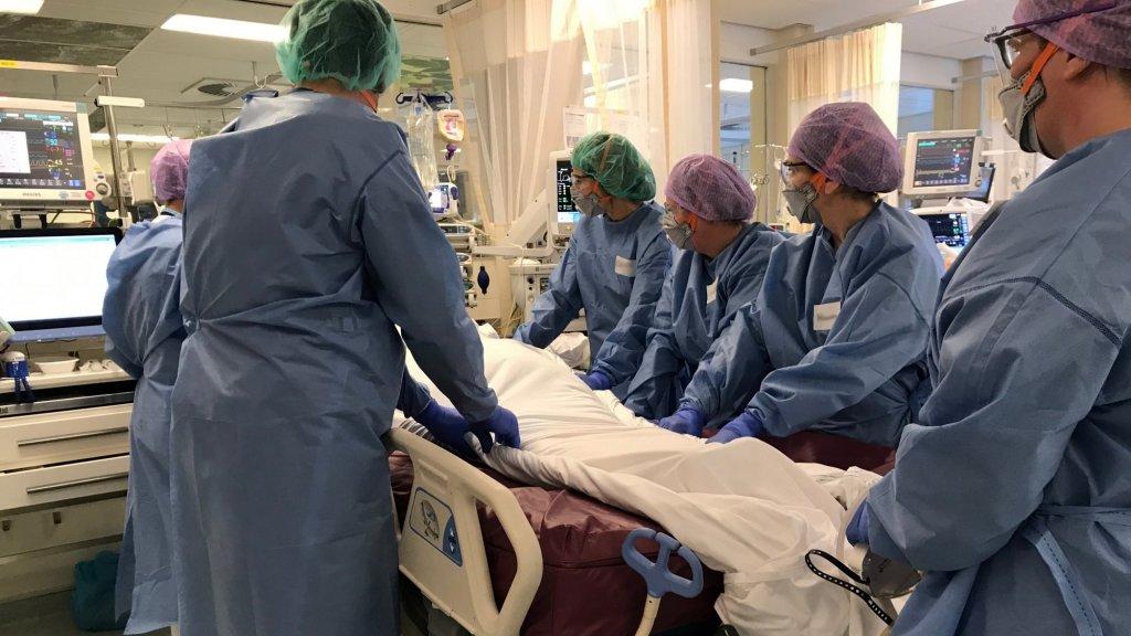 Mama draait samen met haar collega's een patiënt op haar rug.