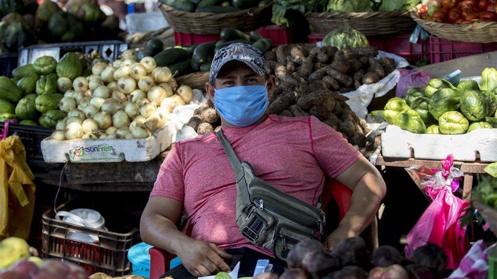 Een groenteverkoper heeft zelf maatregelen genomen en draagt een mondkapje.