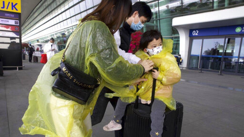 Reizigers met beschermende kleding op het vliegveld in Wuhan