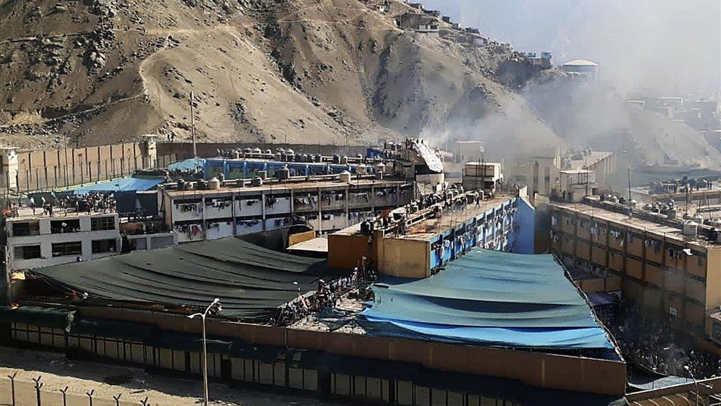 Na de rellen komt er rook uit de gevangenis in Lima.