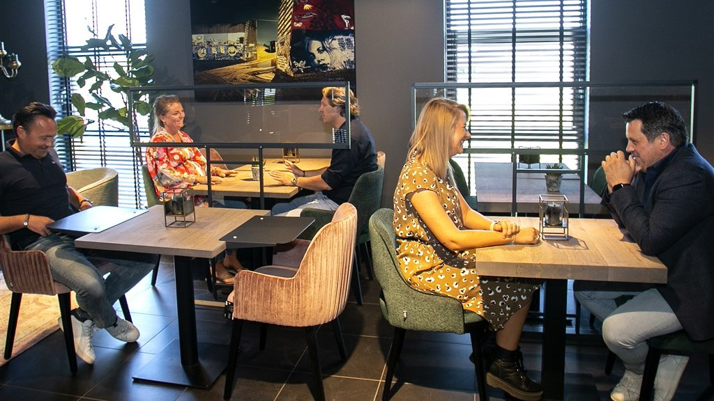 Een restaurant met speciale coronaschermen tussen gasten in.