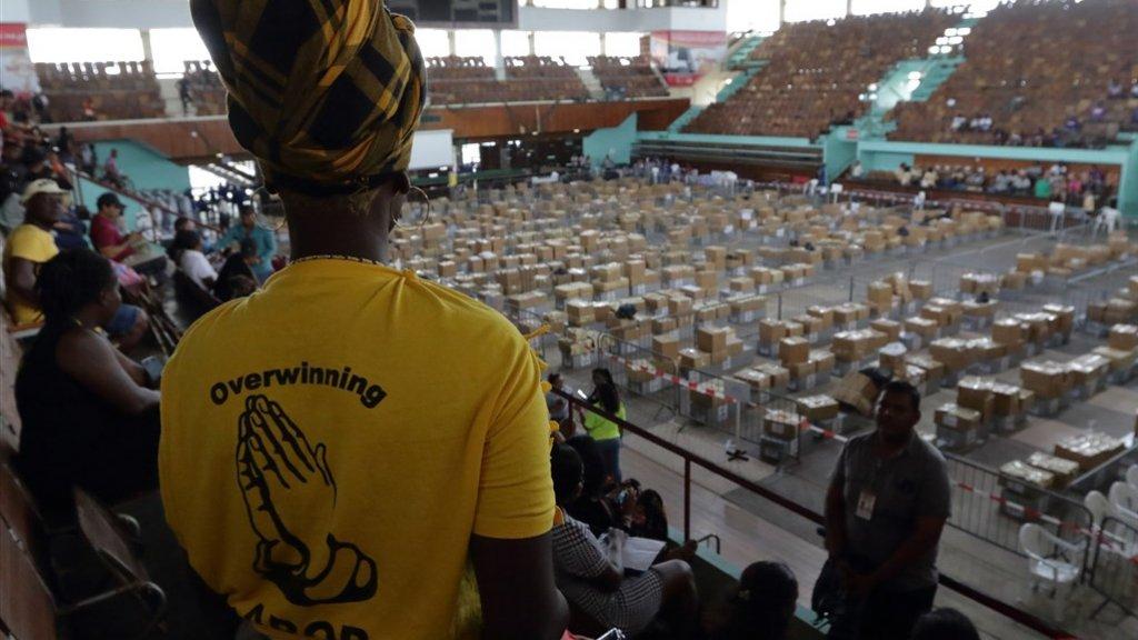 Leden van politieke partijen houden de dozen met stembiljetten in de gaten in de Anthony Nesty Sporthal in hoofdstad Paramaribo.