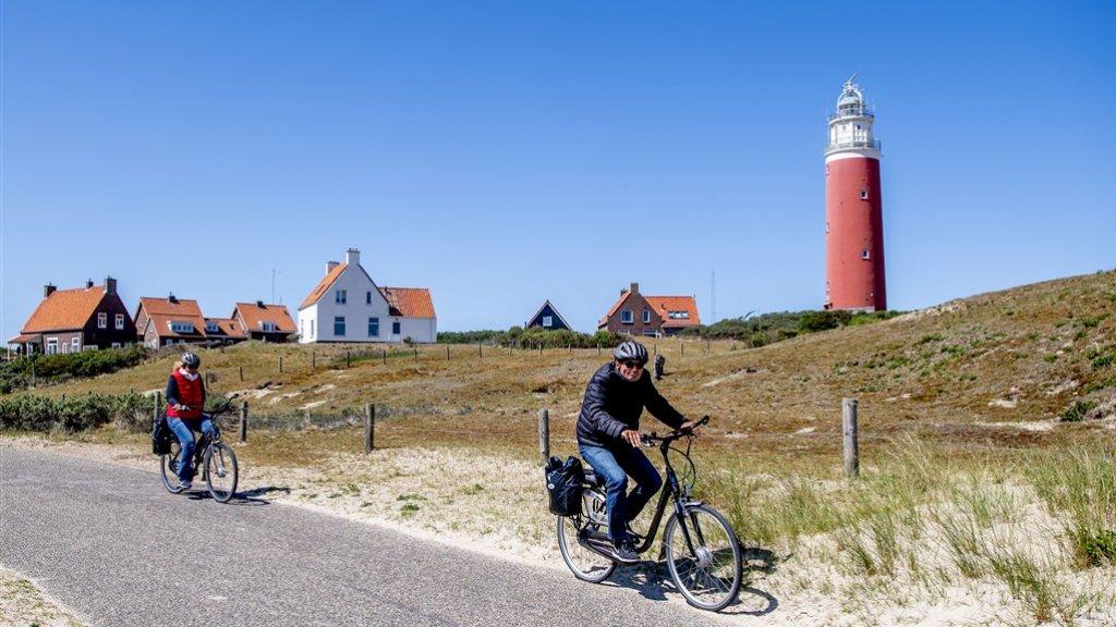Toeristen fietsen langs de vuurtoren op Texel.