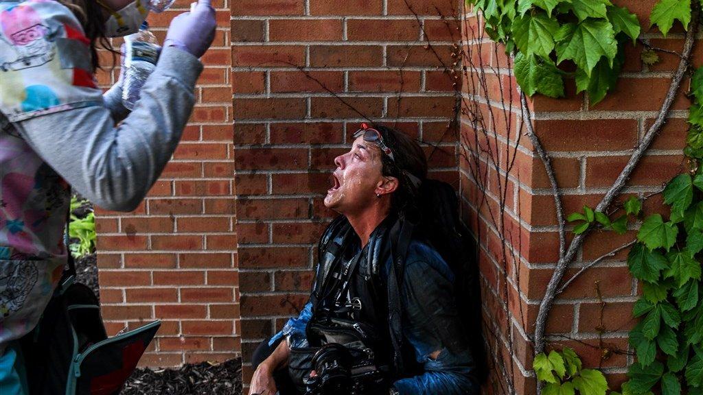 Een demonstrant helpt een journalist die is geraakt door pepperspray.
