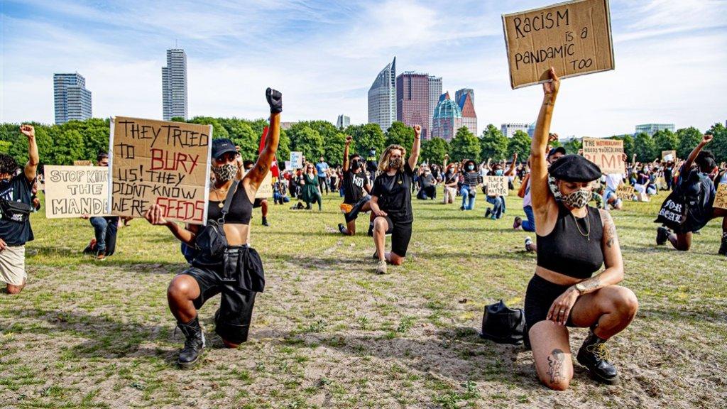 """""""Racism is a pandemic too"""", staat op het bord van een demonstrant op het Malieveld in Den Haag. Het veld is vanavond halfvol gestroomd."""