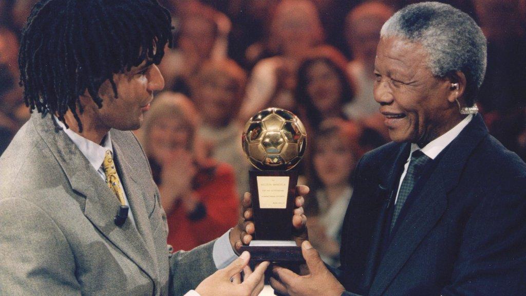 Ruud Gullit overhandigt ANC-leider Nelson Mandela de Gouden Bal, die Gullit in 1987 kreeg toen hij onderscheiden werd tot Europees voetballer van het jaar. Mandela was donderdagavond hoofdgast in het tv-programma 'Geef Zuid-Afrika een eerlijke kans'.