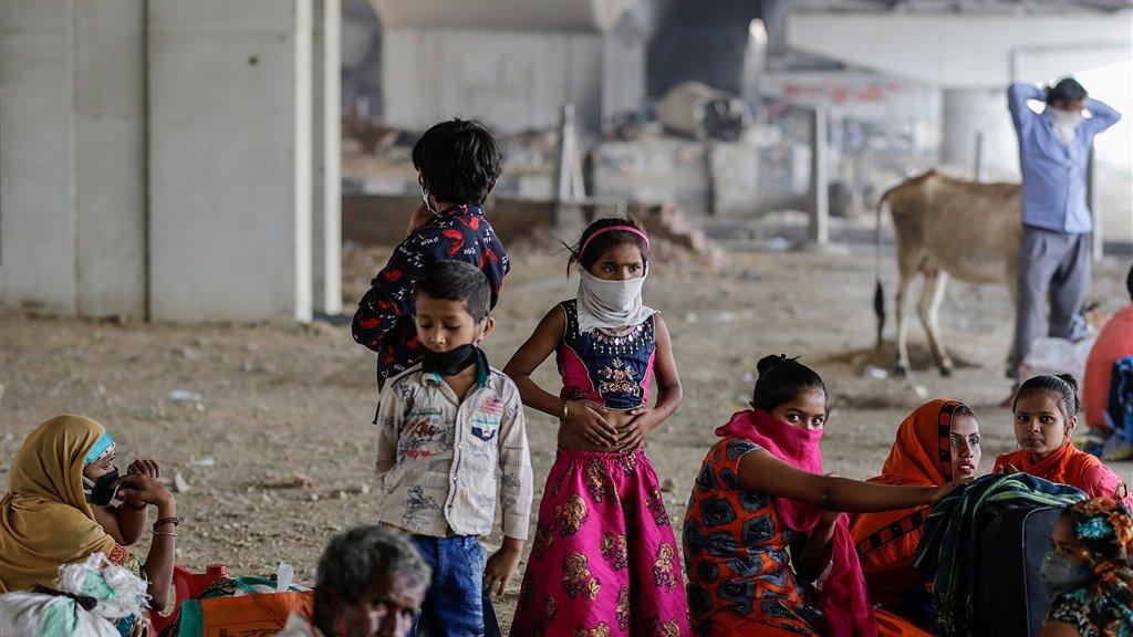 Familie wacht om terug te keren naar hun geboortedorp, nu in de stad geen werk meer is. Zo verspreidt corona door heel India.