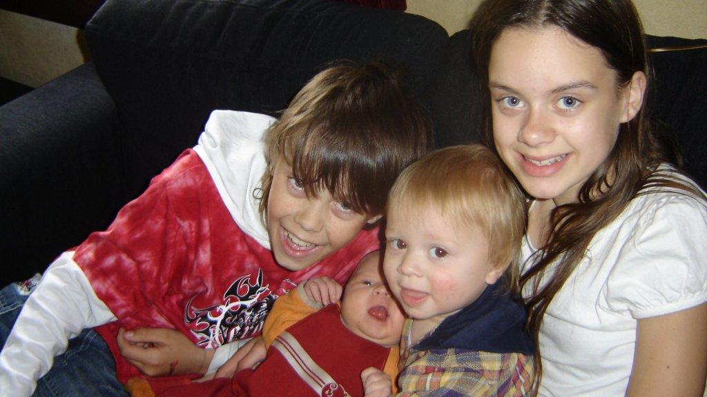 Sidney (links) als kind, samen met zijn twee broertjes en zus.