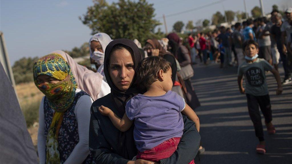 Migranten staan in de rij voor voedsel.