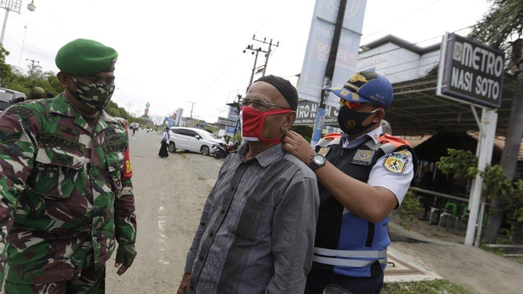 Indonesische soldaat en agent doen bij een man een mondkapje om