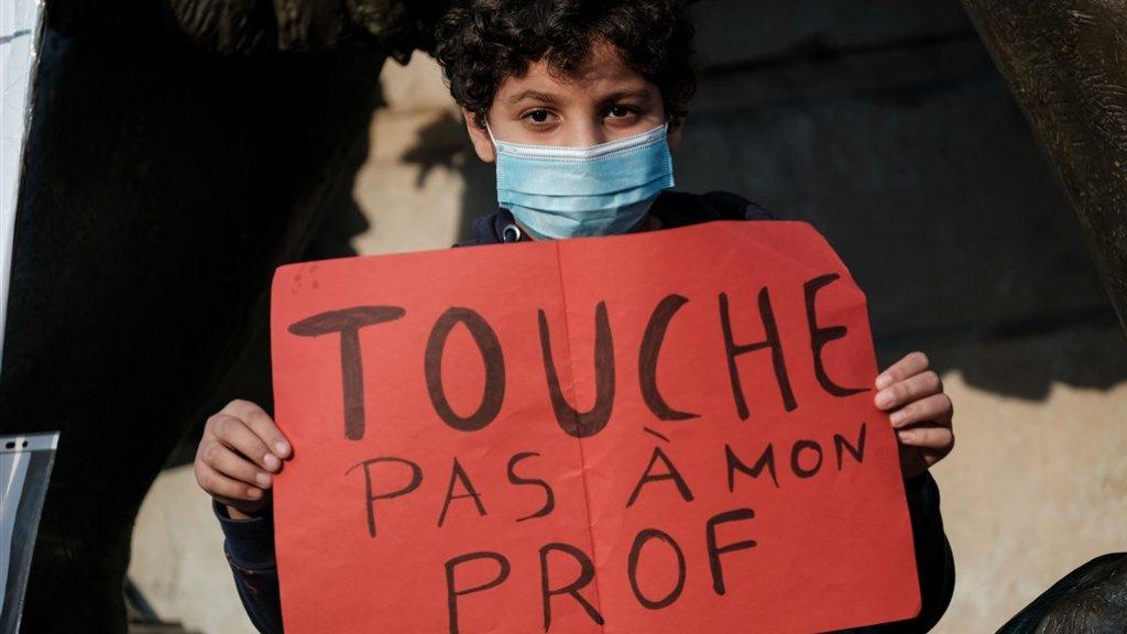 Demonstranten hebben tientallen leuzen opgeschreven. Zoals deze jongen: 'Kom niet aan mijn leerkracht'.