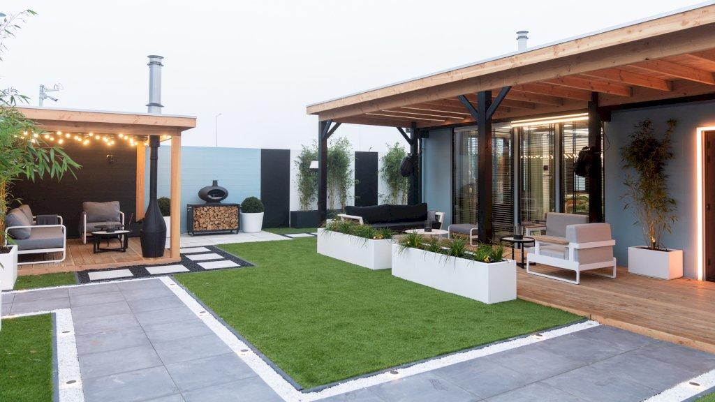 Comfortabele stoelen en banken rondom een kunstgrasmat: de tuin van het Big Brother-huis.