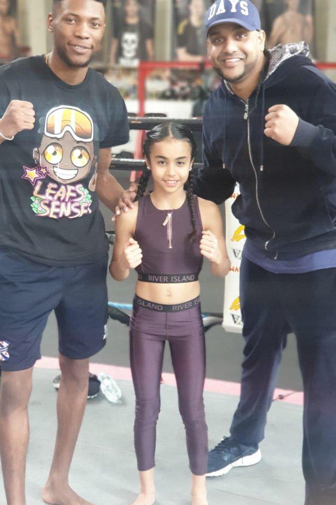 Amira gaat op de foto met volwassen kickbokstalenten.