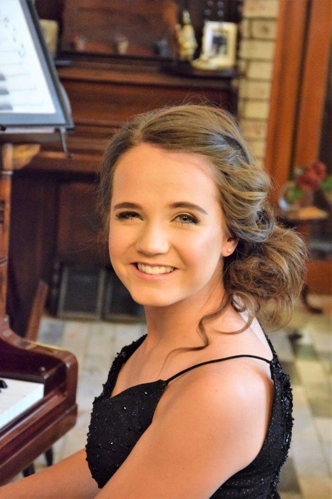 Zo ziet de inmiddels 16-jarige Amira er nu uit, achter de piano.