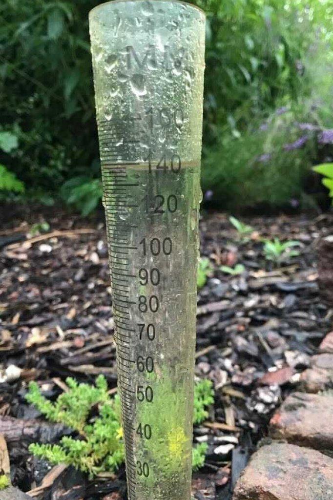 Een regenmeter in een tuin in Bunde: daar viel 140 millimeter regen in 1,5 uur.